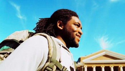 low angle close-up of a young man carrying a backpack and smiling